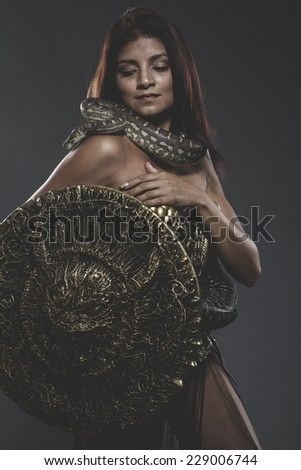 Sensual tattooed woman with big snake and iron corset - stock photo