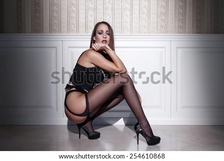 Sensual woman in black underwear squat at night - stock photo