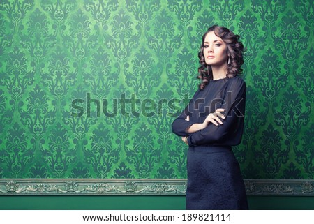 Sensual woman in green vintage interior. Professional make up and hairstyle. Studio lighting. Toned image - stock photo