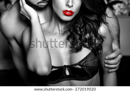 Sensual woman in underwear with young lover, passionate couple foreplay closeup, black and white, selective coloring - stock photo
