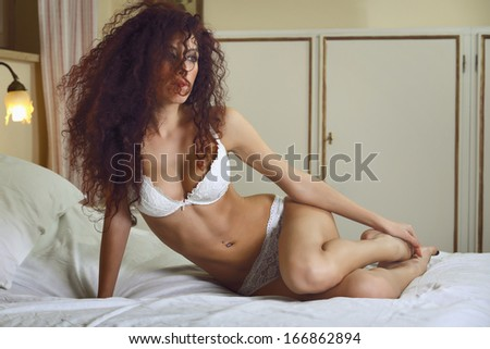Sensual woman in white lingerie relaxing on bed . Boudoir and sexy concept