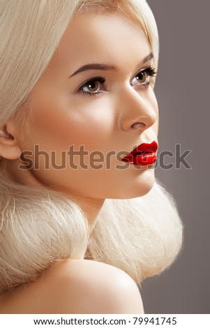 Sensual woman model with fashion bright red lips make-up, clean healthy skin and blond creative hair style