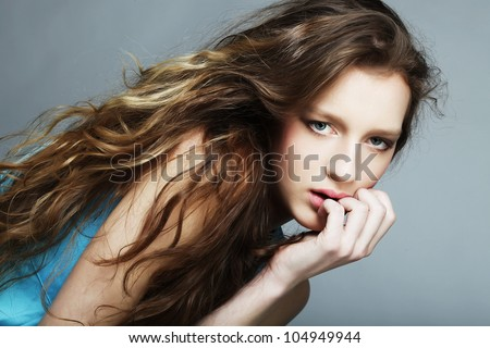 Sensual woman model with windswept flying brunette hair on light gray background. Shiny long health hairstyle. Beauty and haircare. Natural fashion make-up - stock photo