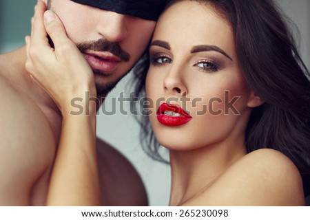 Sensual woman playing with young macho lover, closeup - stock photo