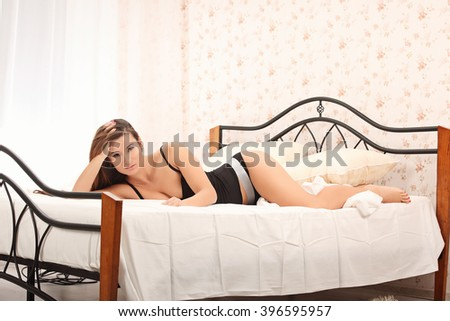 Sensual woman posing with lingerie in bed studio