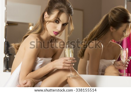 sensual woman preparing for the new year party in bathroom and drinking champagne. Sitting near mirror with naked body under white towel, glass in the hand.  - stock photo