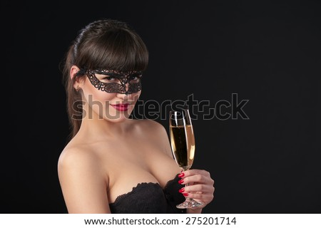 Sensual woman wearing black masquerade carnival mask at party holding a glass with champagne. Closeup portrait with copy space  - stock photo