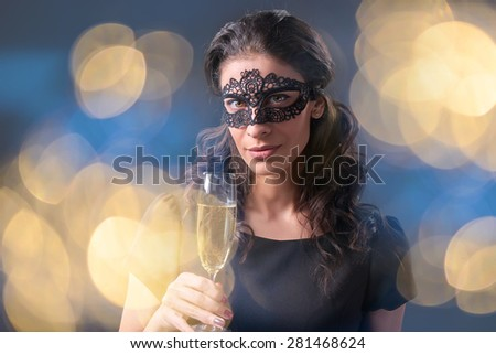 Sensual woman wearing black masquerade carnival mask at party holding a glass with champagne over holiday bokeh background. Closeup portrait with copy space - stock photo