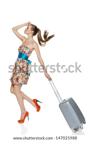 Sensual woman wearing light chiffon dress walking with suitcase in full length against white background - stock photo