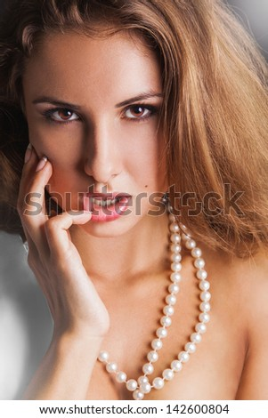 Sensual woman with brown eyes looking at camera in studio - stock photo