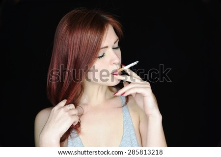 Sensual woman with closed eyes and red hair, smoking a Cigarette and touching her hair on Black Background. Fine art portrait of a beautiful lady with cigarette  - stock photo