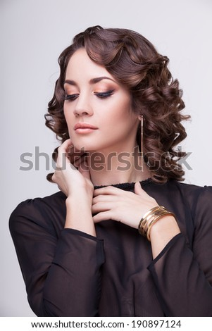 Sensual woman with hands on her neck. Professional make up and hairstyle. Studio lighting