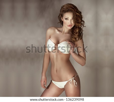 Sensual woman with perfect body wearing fashionable white swimwear posing, looking at camera. Long curly hair, beautiful breast. - stock photo