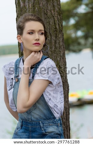 sensual woman with urban style posing in the nature near tree with lake water on background. Wearing denim overalls and trendy t-shirt. stylish make-up  - stock photo