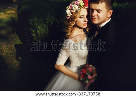 Sensual young blonde bride in white dress hugging romantic groom at sunset - stock photo