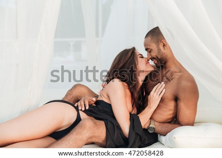 Sensual young couple kissing and embracing on white bed