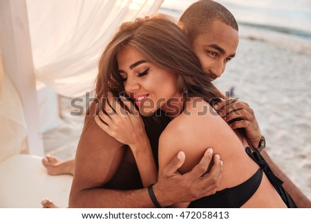 Sensual young couple relaxing and embracing on the beach