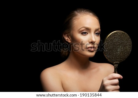 Sensual young female model looking in hand mirror. Beautiful young girl checking her make up against black background with copyspace. - stock photo
