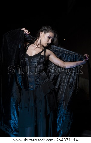 Sensual young girl dressed in black coat with gothic style - stock photo