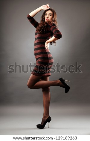 Sensual young girl in full length glamour pose, on gray background