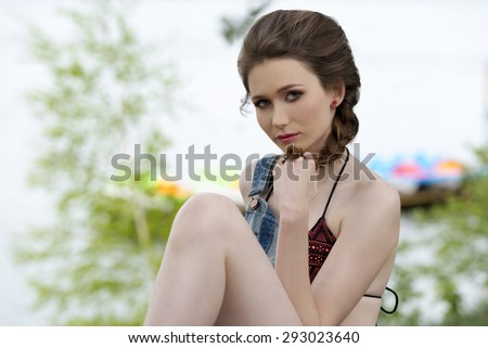 sensual young girl posing in outdoor summer shoot with cute bikini under denim overall and braid hair-style. With green tree and sea water on background  - stock photo