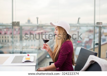 Sensual young lady drinking red wine posing at cafe with a great view of the city,lounge bar,skyline,red lipstick smile,red wine ,fancy woman,lovely fashionable style,teen fashion,fashion accessory  - stock photo