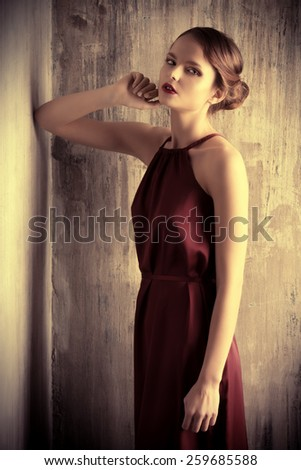 Sensual young lady in red dress posing an studio. Beauty, fashion concept.