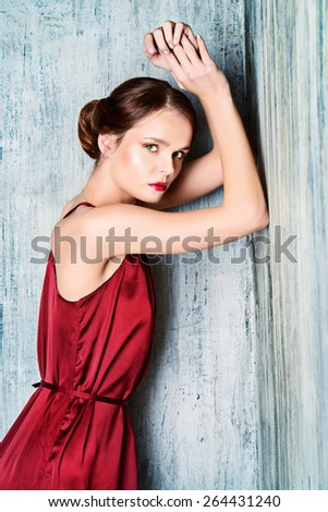 Sensual young lady in red dress posing an studio. Beauty, fashion concept. - stock photo