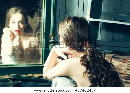 Sensual young lady with bare chest and curly hair near old dirty vintage mirror