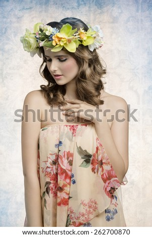 sensual young lady with brown natural hair-style and make-up wearing floral dress and some colorful flowers on head. Spring atmosphere   - stock photo