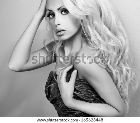 sensual young lady with long curly hair and bright make up looking at camera black and white portrait