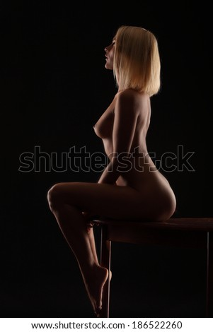 sensual young naked brunette girl posing with her perfect body on small table wearing sexy white lingerie and heels. Backlight glamour portrait  - stock photo