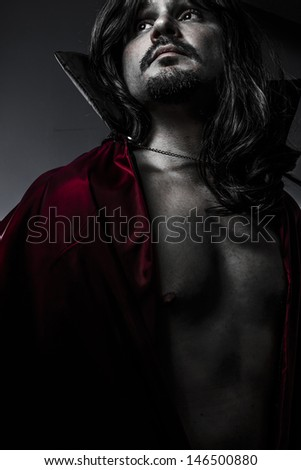 Sensual Young Vampire with black coat and long hair, nude - stock photo
