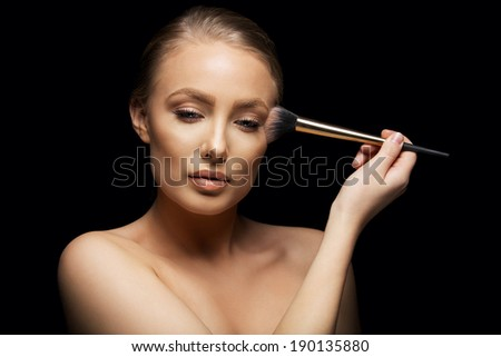 Sensual young woman applying make up with a brush against black background. Pretty young caucasian model. - stock photo