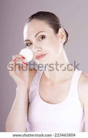 Sensual young woman cleaning skin with  cotton swab, over gray background. Skin care concept.