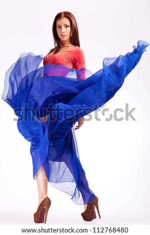 sensual young woman in a blue fluttering dress looking at the camera - stock photo