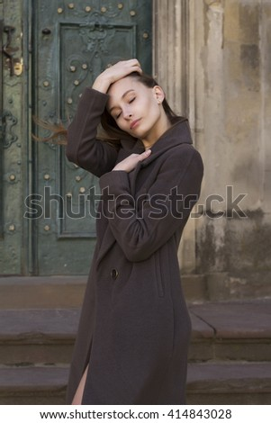 Sensual young  woman in a grey coat at the street - stock photo