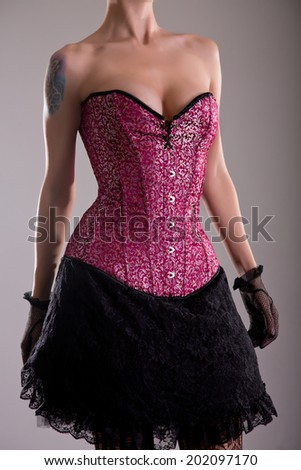 Sensual young woman in purple corset with floral pattern, studio shot  - stock photo