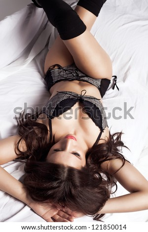 Sensual young woman lying on the bed, studio shot - stock photo