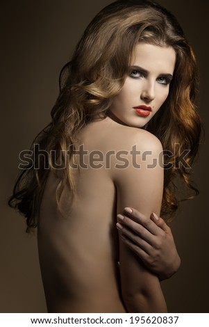 sensual young woman posing with long wavy hair, charming make-up and naked shoulders