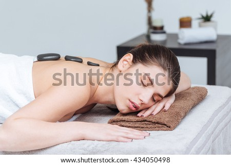 Sensual young woman relaxing and receiving hot stone massage in spa salon - stock photo