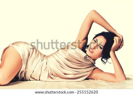 Sensual young woman with beautiful body in the beige silk over white background - stock photo