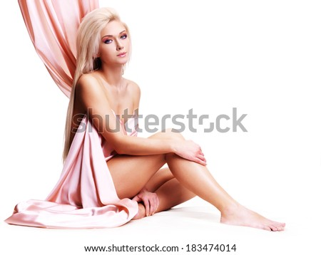 Sensual young woman with beautiful body in the pink silk sitting over white background.