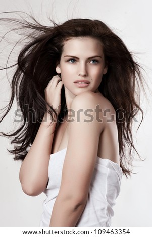 Sensual young woman with beautiful long brown flying hairs, posing i