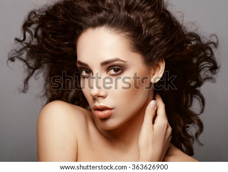 Sensual young woman with delicate makeup and curly brown hair. Healthcare. Perfect skin. Beauty face.  - stock photo