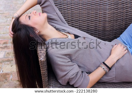 Sensual young woman with long dark hair, relaxing on a rattan armchair on terrace - stock photo