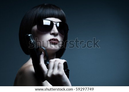 sensuality  beautiful  girl, close face , with pistol, on dark background, glamour blue light - stock photo