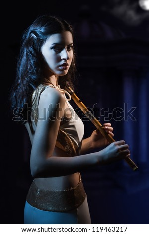 Sensuality beauty brunette with a wooden flute