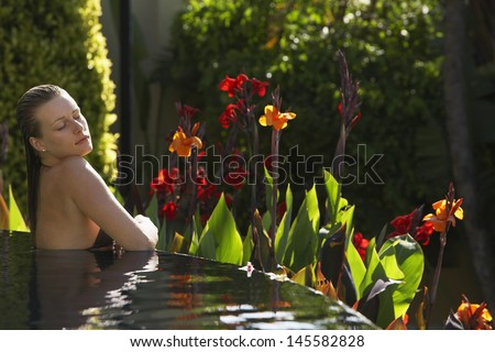 Sensuous young woman in outdoor swimming pool - stock photo