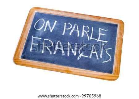 sentence french is spoken written in french on a chalkboard - stock photo